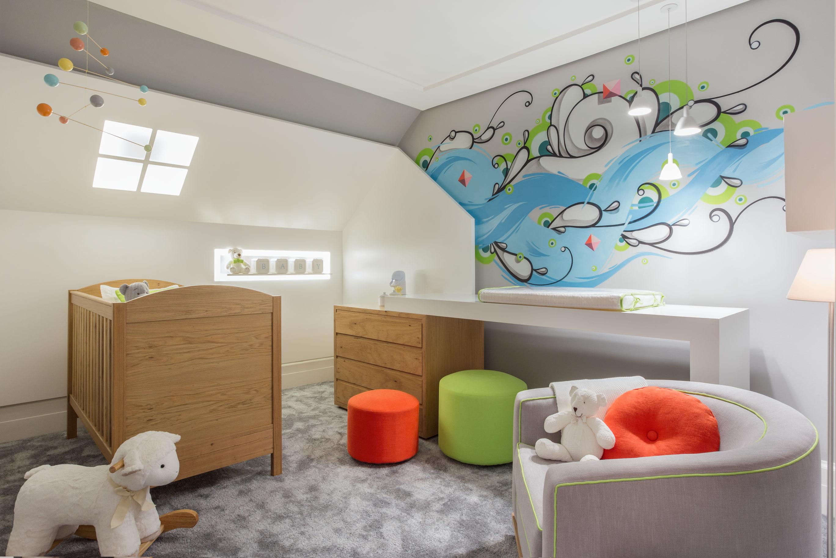 O profissional criou um quarto de bebê bem urbano, com desenhos em street art do artista Rafael Highraff com cores que remetem ao mar. Marcenaria laqueada aparecem nas paredes baseado nos tradicionais lambris